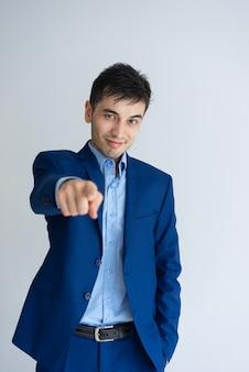 Pozytywny biznesowy mężczyzna wskazuje przy tobą i patrzeje kamerę