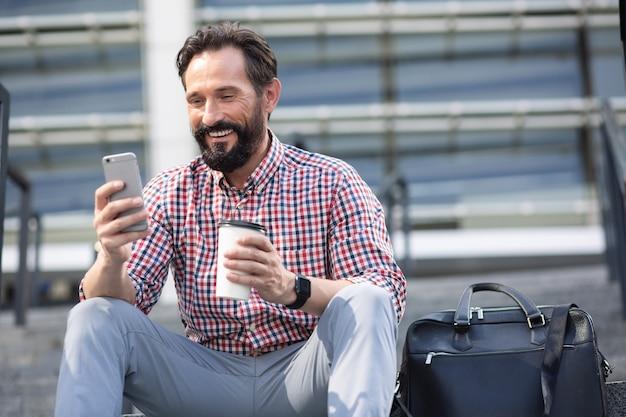 Pozytywny brodaty dorosły mężczyzna siedzi w miejskim otoczeniu, pijąc kawę i używając telefonu