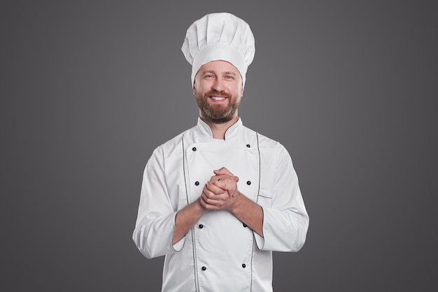 Pozytywny brodaty dorosły mężczyzna w mundurze szefa kuchni, uśmiechając się do kamery i pocierając ręce podczas pracy w restauracji na szarym tle