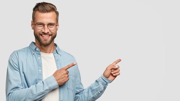 Pozytywny brodaty facet pozuje przy białej ścianie