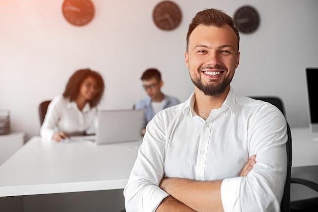 Pozytywny, brodaty inżynier oprogramowania ze skrzyżowanymi rękami, uśmiechając się i patrząc na kamery podczas pracy w międzynarodowym zespole we współczesnym biurze