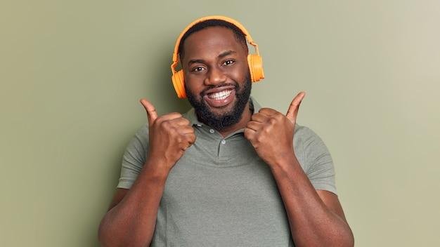 Pozytywny brodaty mężczyzna lubi playlistę trzyma kciuki do góry, robi gest aprobaty słucha muzyki przez słuchawki uśmiecha się zębami ubrany w swobodną koszulkę odizolowaną na ciemnozielonej ścianie