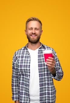 Pozytywny brodaty mężczyzna w kraciastej koszuli, uśmiechając się do kamery i niosąc na wynos kubek gorącego napoju rano na żółto