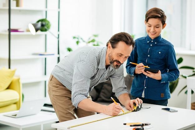 Pozytywny brodaty mężczyzna w średnim wieku pochylający się nad stołem i uśmiechający się, rysując linie za pomocą taśmy mierniczej, a jego optymistyczny syn stojący w pobliżu