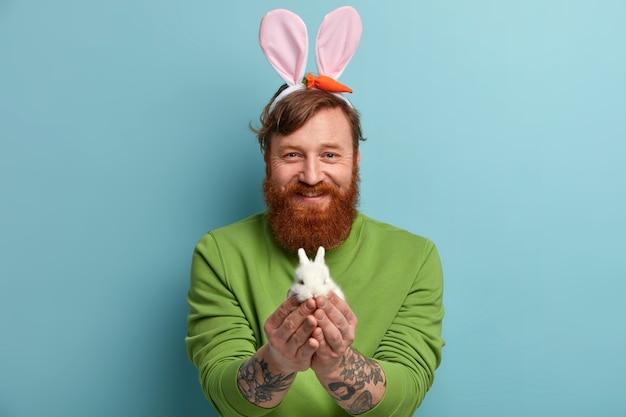 Pozytywny brodaty mężczyzna z rudymi włosami trzyma maleńkiego białego króliczka wściekłości