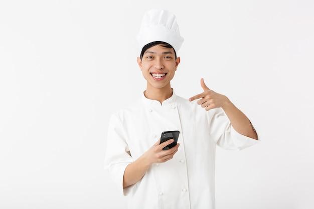 Pozytywny chiński wódz w białym mundurze kucharza i kapelusz szefa kuchni trzymając telefon komórkowy na białym tle nad białą ścianą