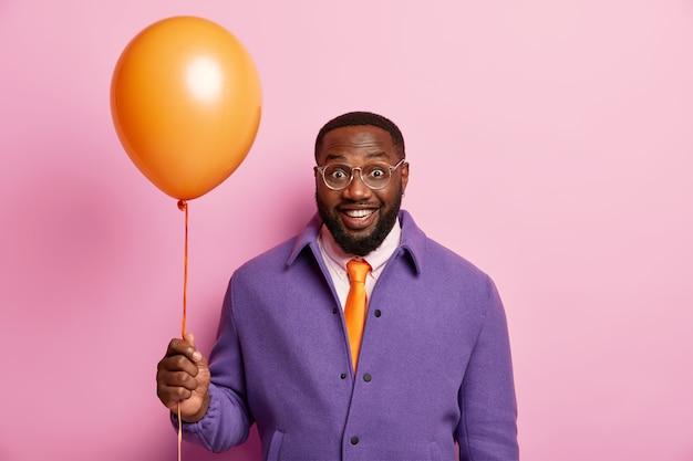 Pozytywny człowiek przychodzi na uroczyste spotkanie z przyjaciółmi, cieszy się wakacjami, stoi z pomarańczowym balonem, ma dobry humor