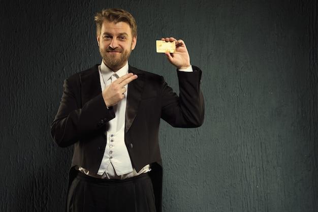 Pozytywny człowiek w fraku wskazującym palcem na kartę kredytową.