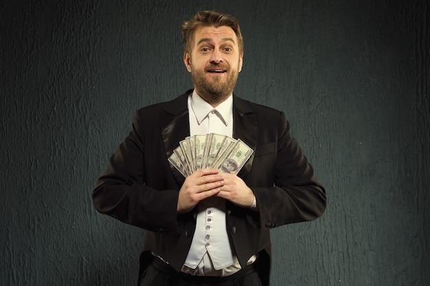 Pozytywny człowiek we fraku trzyma pieniądze.