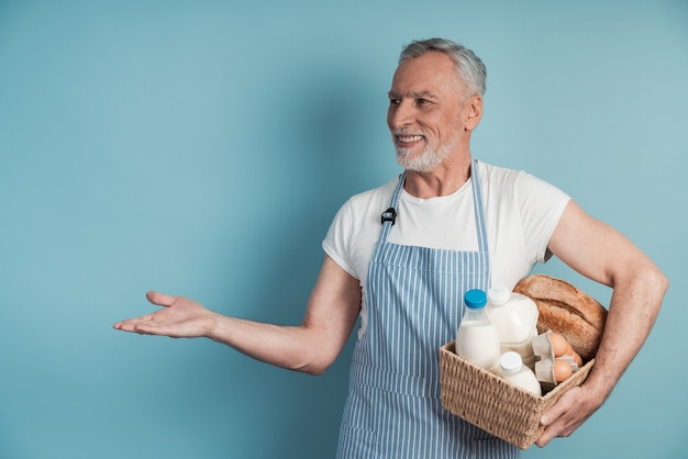 Pozytywny człowiek z siwymi włosami i brodą, trzymając kosz z jedzeniem pokazuje na przestrzeni kopii, miejsce na tekst