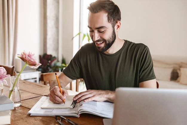 Pozytywny dojrzały mężczyzna w zwykłej odzieży, zapisujący notatki na papierze i korzystający z laptopa podczas pracy w mieszkaniu