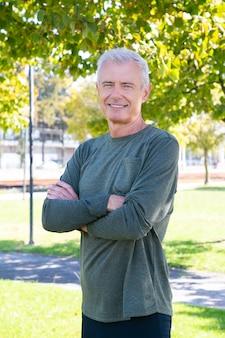 Pozytywny dojrzały mężczyzna ze skrzyżowanymi rękami stojący na zewnątrz, uśmiechnięty i uśmiechnięty. strzał w pionie. dojrzała sportowa osoba lub koncepcja aktywnego stylu życia