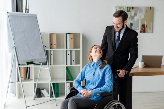 Pozytywny dorosły mężczyzna i kobieta przy biurem