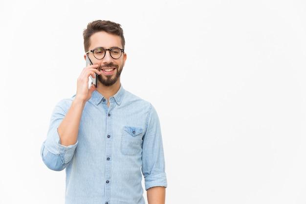 Pozytywny facet opowiada na telefonie komórkowym