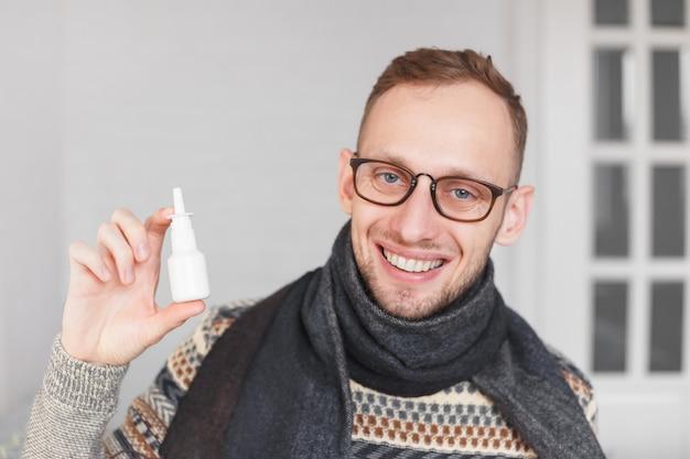 Pozytywny facet pokazujący spray do nosa lub oczu