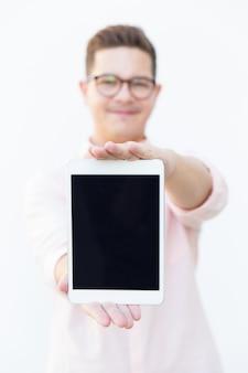 Pozytywny facet w eyeglasses pokazuje pustego pastylka ekran