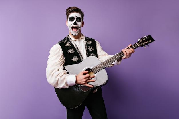Pozytywny facet w tradycyjnym meksykańskim stroju śpiewa serenadę. migawka emocjonalnego człowieka z gitarą w ręku.