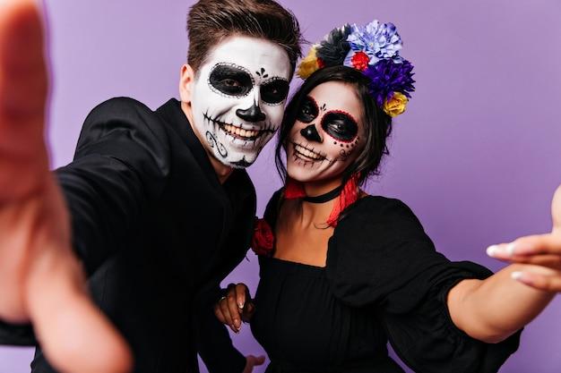 Pozytywny facet zombie robi selfie w studio z dziewczyną. szczęśliwi przyjaciele w kostiumach maskarady dobrze się bawią.