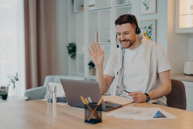 Pozytywny freelancer korzystający z laptopa w domu, siedzący przy drewnianym stole i prowadzący konferencję online z kolegami podczas pracy zdalnej, machający do nich. koncepcja pracy niezależnej i zdalnej