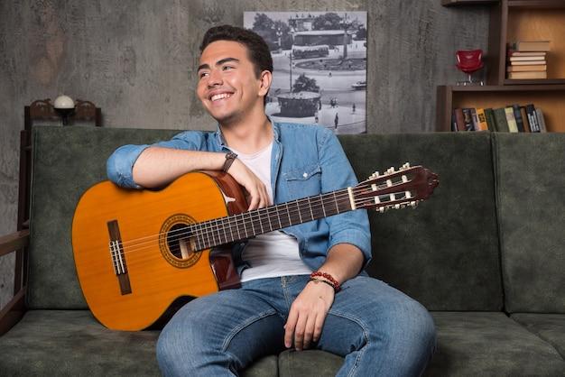Pozytywny gitarzysta trzyma piękną gitarę i siedzi na kanapie. wysokiej jakości zdjęcie