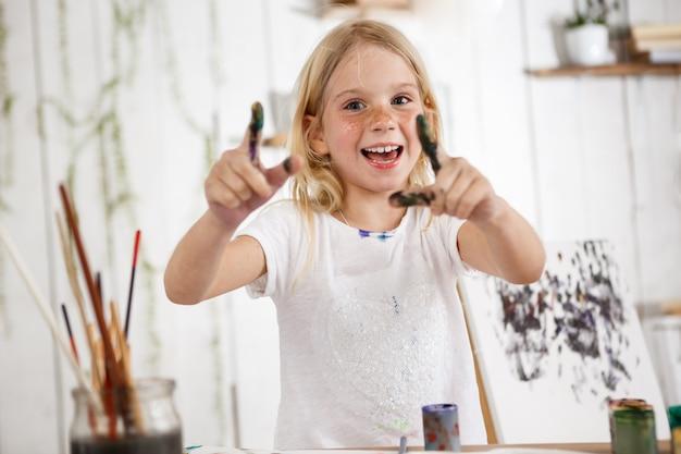 Pozytywny i pełen radości, uśmiechnięty zębami blond europejskie dziecko płci żeńskiej wskazujące palcami w farbie.