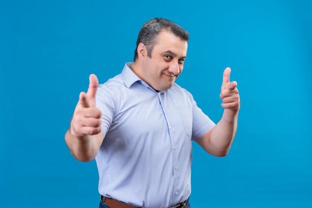 Pozytywny i uśmiechnięty mężczyzna w średnim wieku w niebieskiej koszuli w paski, wskazując palcem wskazującym na aparat na niebieskim tle