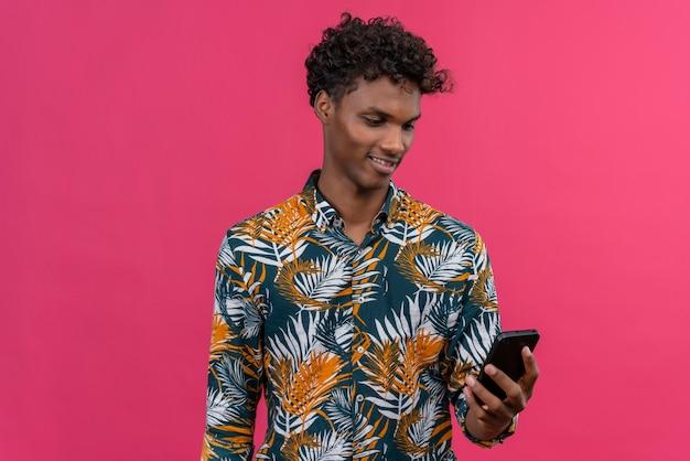 Pozytywny i uśmiechnięty młody przystojny ciemnoskóry mężczyzna z kręconymi włosami w koszulce z nadrukiem liści, patrząc na swój telefon komórkowy