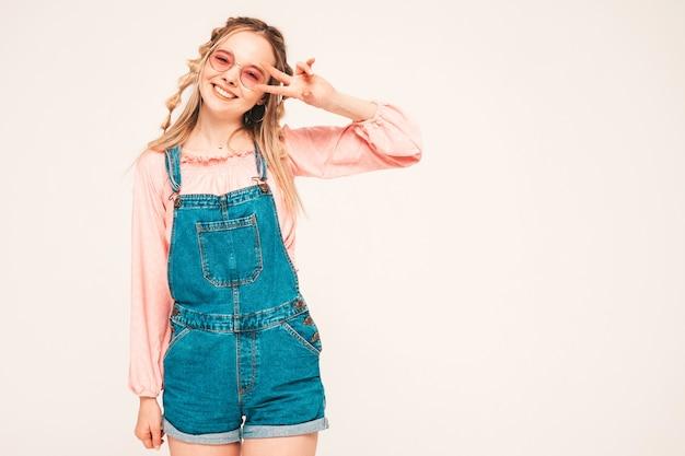 Pozytywny i zabawny model pozujący na szarej ścianie w studio w okularach przeciwsłonecznych