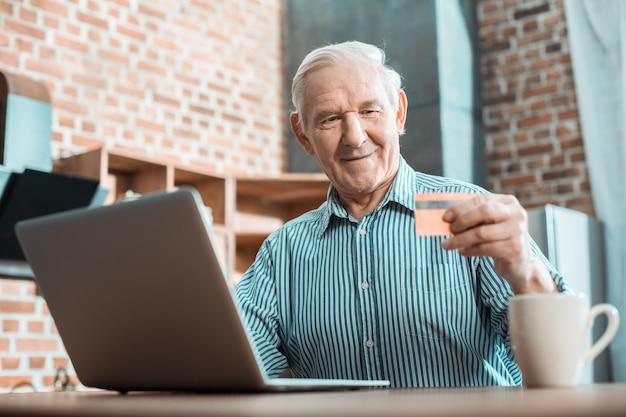 Pozytywny inteligentny starszy mężczyzna siedzący przed komputerem i patrząc na kartę kredytową, ucząc się obsługi systemu bankowości internetowej