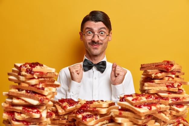Pozytywny klient cieszy się all inclusive w restauracji, stoi przy stosie pysznych tostów, nosi elegancką białą koszulę i muszkę, zaciska pięści,