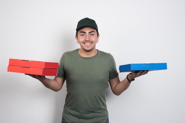 Pozytywny kurier przewożący pudełka po pizzy na białym tle.