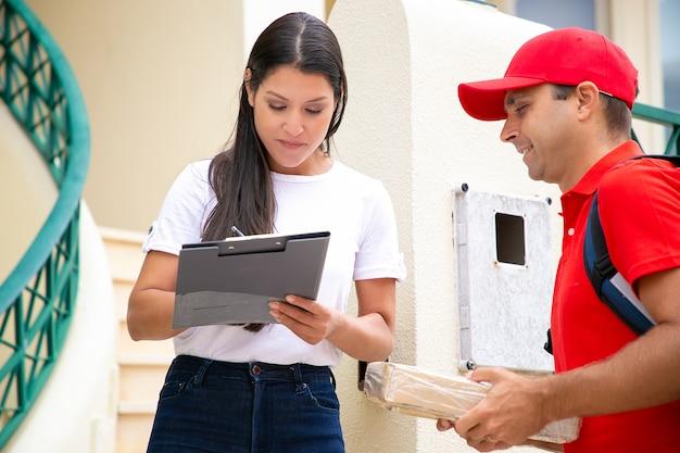 Pozytywny kurier w jednolitej paczce dostarczającej pod drzwi klienta. kobieta do podpisania odbioru paczki. koncepcja usługi dostawy lub dostawy