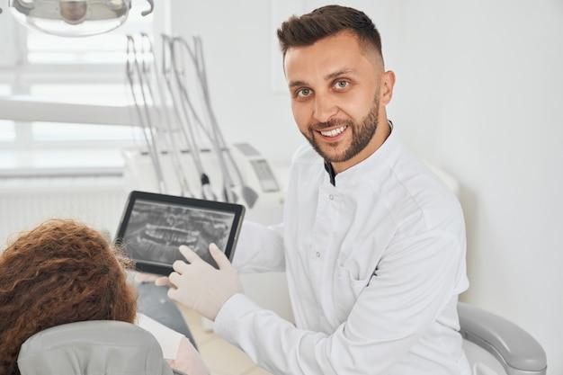 Pozytywny męski dentysta pozuje podczas gdy konsultujący żeńskiego pacjenta