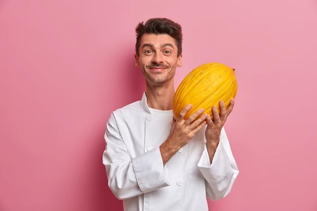 Pozytywny męski szef kuchni posiada duży dojrzały żółty melon