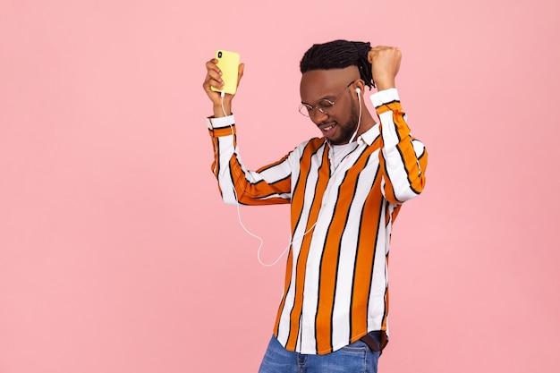 Pozytywny mężczyzna afroamerykański słuchający muzyki lub radia na smartfonie z zestawem słuchawkowym i tańcem