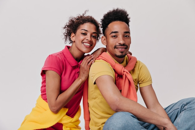 Pozytywny mężczyzna i kobieta patrzący z uśmiechem na kamerę na izolowanej ścianie