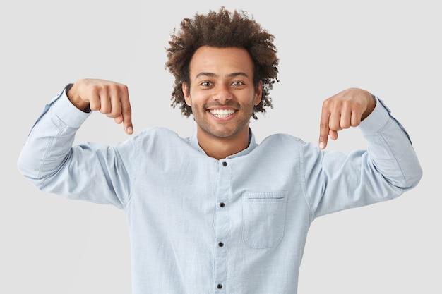 Pozytywny mężczyzna o kręconych włosach, wskazujący dwoma przednimi palcami w dół, reklamuje nowy materiał na podłogę, ma szeroki uśmiech, pokazuje idealnie równe zęby