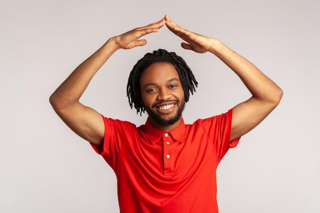 Pozytywny mężczyzna podnoszący ręce pokazujący gest dachu i uśmiechający się z zadowoleniem, marzący o domu.