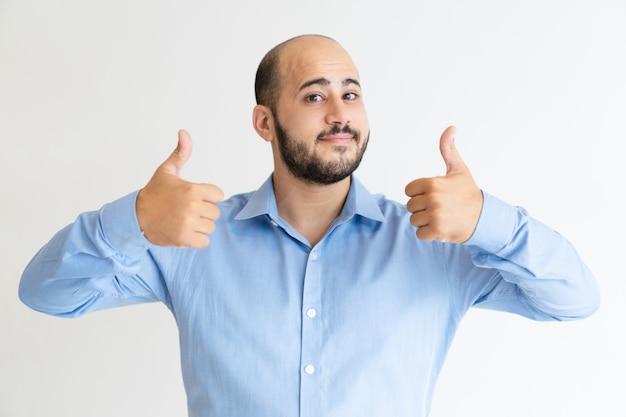 Pozytywny mężczyzna pokazuje oba aprobaty i patrzeje kamerę