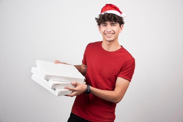 Pozytywny mężczyzna pozuje z pudełkami po pizzy.