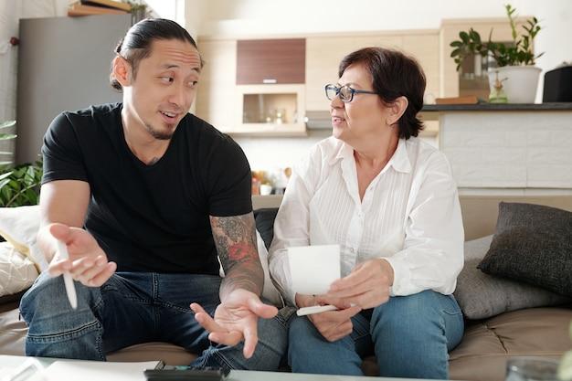 Pozytywny mężczyzna rasy mieszanej wyjaśniający matce, jak płacić rachunki lub rachunki za media online i zarządzać miesięcznymi wydatkami