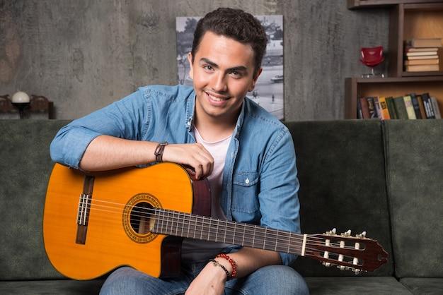 Pozytywny mężczyzna siedzi na kanapie z piękną gitarą. wysokiej jakości zdjęcie
