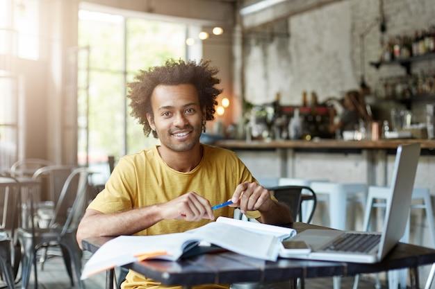 Pozytywny mężczyzna siedzi przy biurku w kawiarni za pomocą laptopa