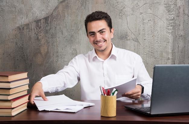 Pozytywny mężczyzna trzyma kartki papieru i siedzi przy biurku. wysokiej jakości zdjęcie