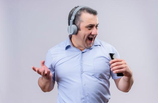 Pozytywny mężczyzna w średnim wieku na sobie niebieską koszulę w pionowe paski za pomocą telefonu komórkowego ze słuchawkami, słuchanie muzyki i śpiew na białym tle