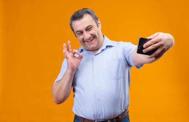 Pozytywny mężczyzna w średnim wieku w niebieskiej koszuli w pionowe paski, śmiejąc się i biorąc selfie na smartfonie na pomarańczowym tle