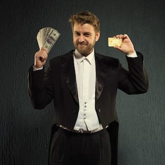 Pozytywny mężczyzna we fraku oferuje kartę kredytową i pieniądze.