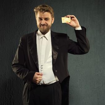 Pozytywny mężczyzna we fraku oferuje kartę kredytową.
