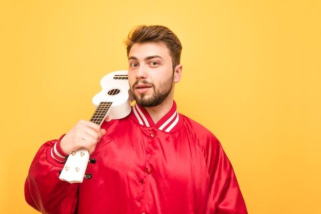 Pozytywny mężczyzna z brodą stojący na żółto z ukulele w rękach