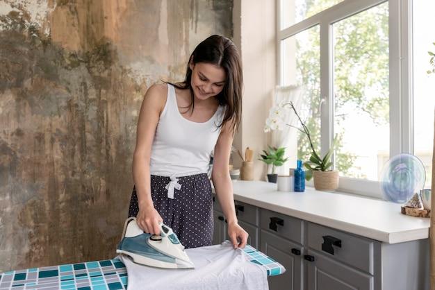 Pozytywny młodej kobiety prasowanie odziewa w domu